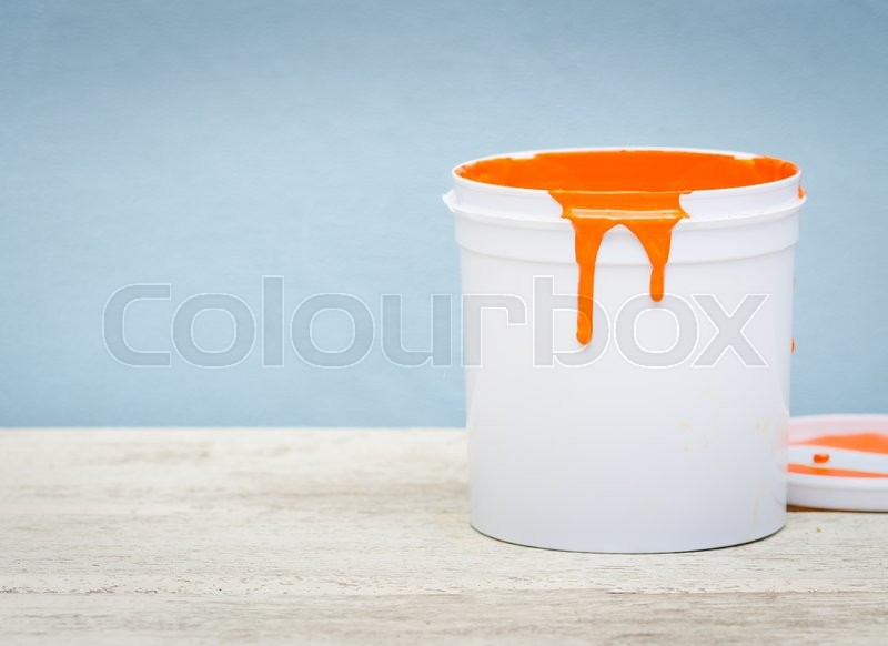Stock image of 'White plastic bucket with orange color paint on wood,vintage background'