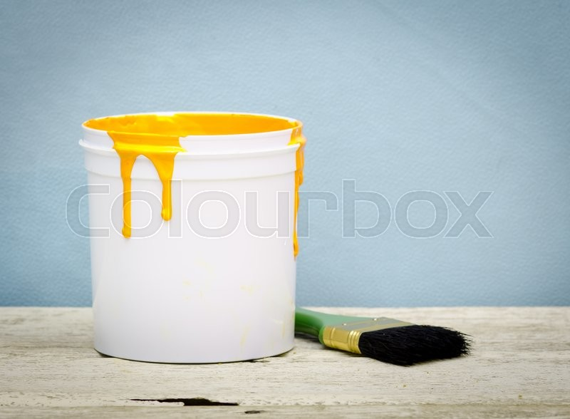 Stock image of 'White plastic bucket with yellow color paint and brush on wood,vintage background'