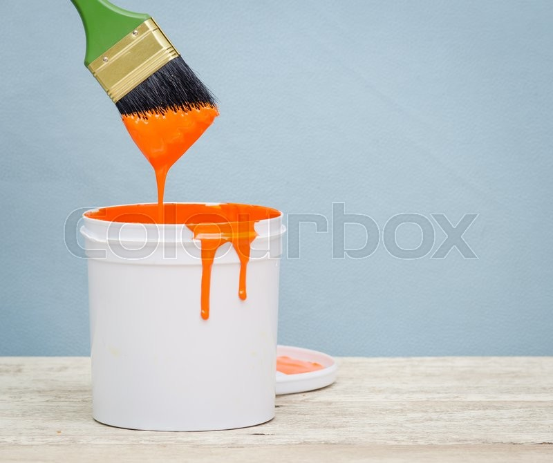 Stock image of 'White plastic bucket with orange color paint and brush on wood,vintage background'