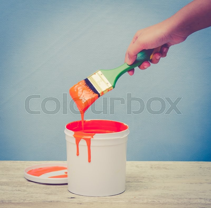 Stock image of 'Hand holding the paint brush and White plastic bucket with orange color on wood,vintage color toned image'