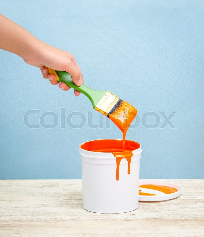 Stock image of 'Hand holding the paint brush and White plastic bucket with orange color on wood,vintage background'