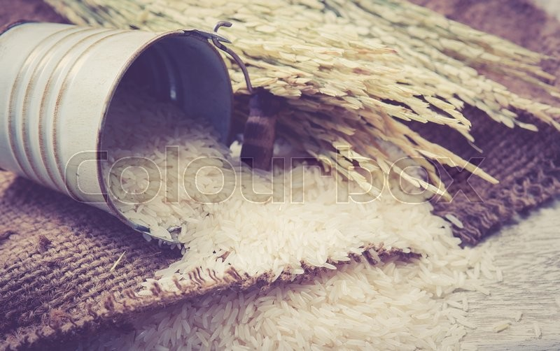 Stock image of 'White rice and paddy pile on wood background; vintage tone style'