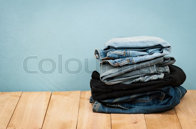 Stock image of 'Stack of jeans on wooden vintage background'