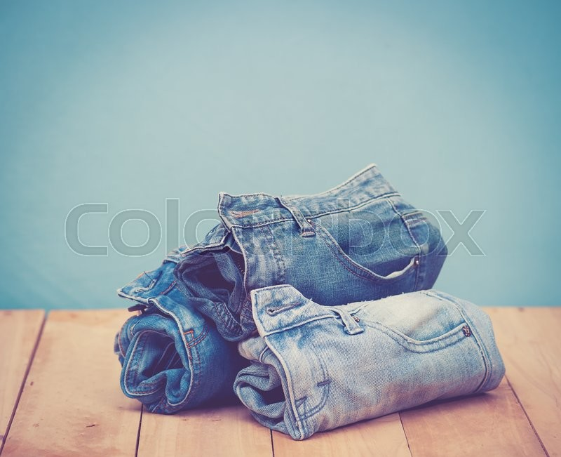 Stock image of 'Stack of jeans on wooden vintage background; vintage tone style'