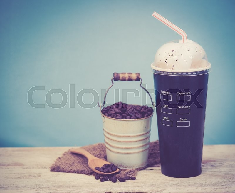 Stock image of 'Iced coffee with coffee beans on wood vintage background,Selective focus on paper cup,vintage tone style'