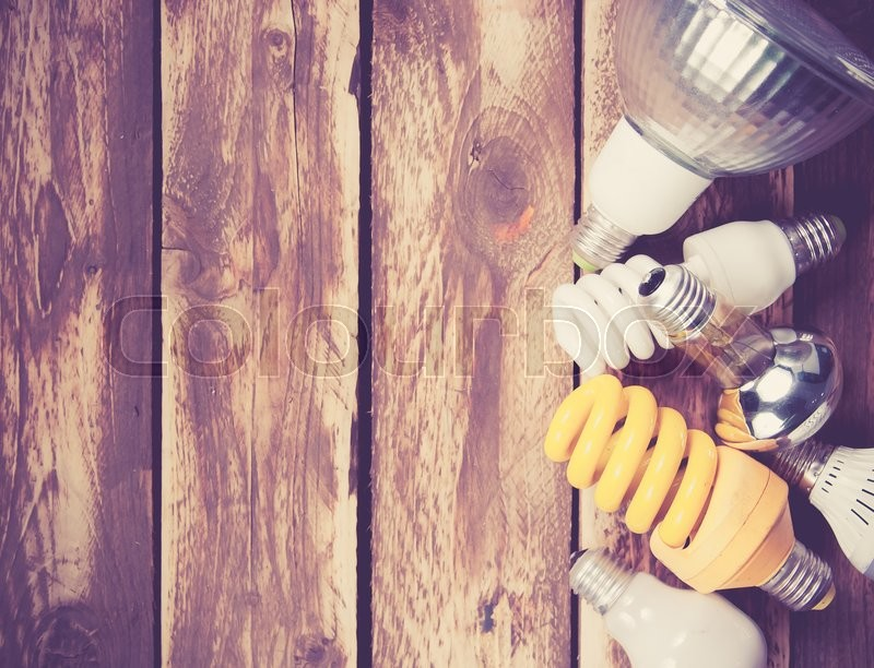 Stock image of 'Different lightbulbs on wooden background,top view,vintage color toned image'