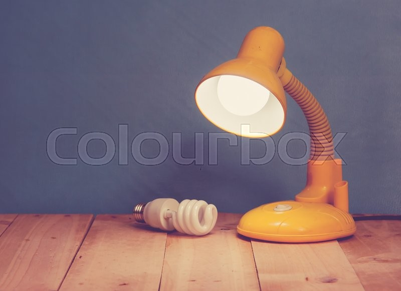 Stock image of 'Table lamp on wooden background,vintage color toned image'
