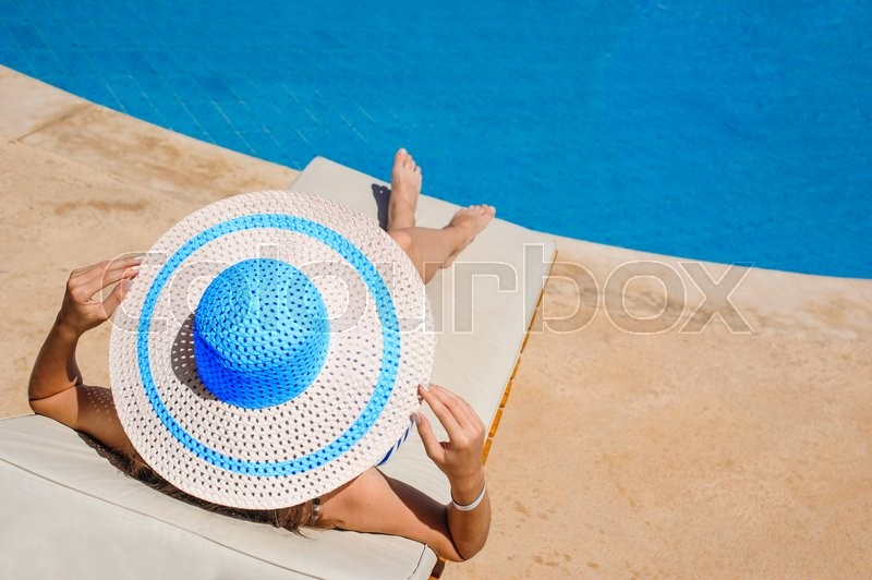 Stock image of 'happy woman with hat sunbathing on a sun lounger by the pool.'