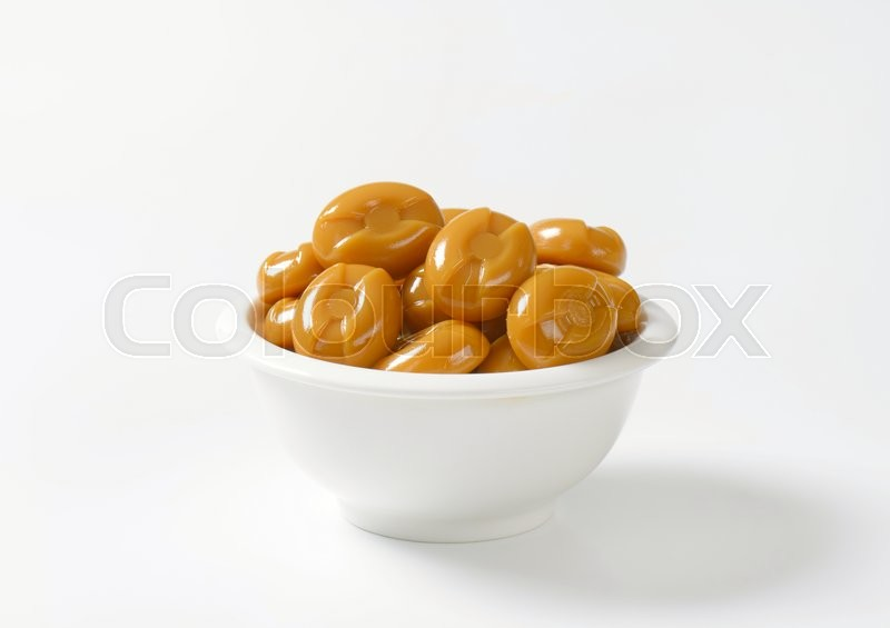 Stock image of 'bowl of caramel candies on white background'