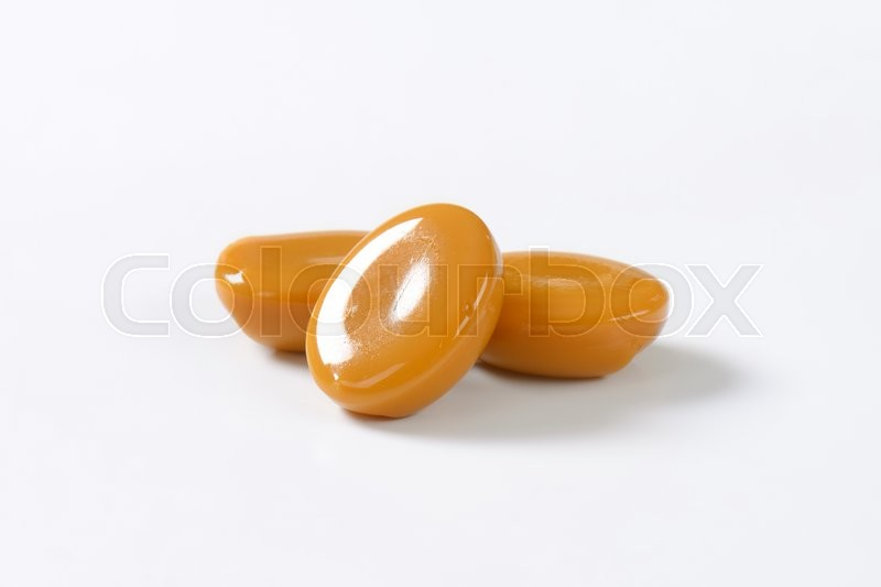 Stock image of 'three caramel candies on white background'