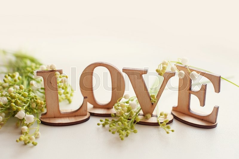 Stock image of 'wooden word love with lilies and place for your text.'
