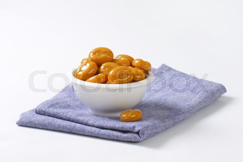 Stock image of 'bowl of caramel candies on blue tablecloth'