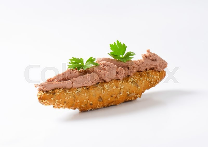 Stock image of 'Wholegrain bread roll with liver pate'