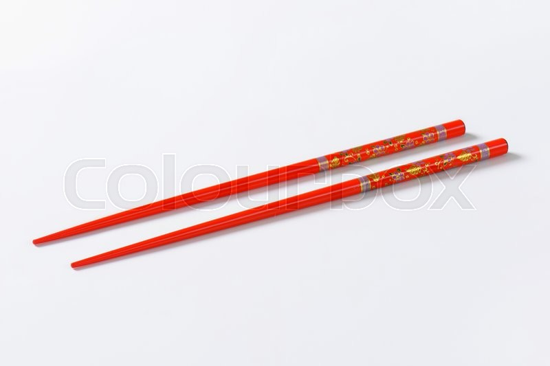 Stock image of 'A pair of red chopsticks with floral pattern'