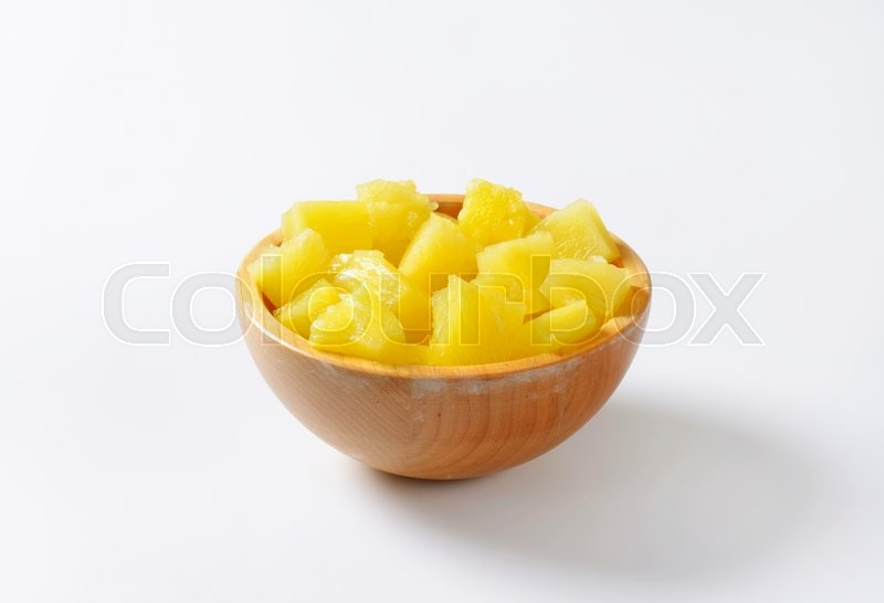 Stock image of 'Bowl of pineapple pieces in light syrup'