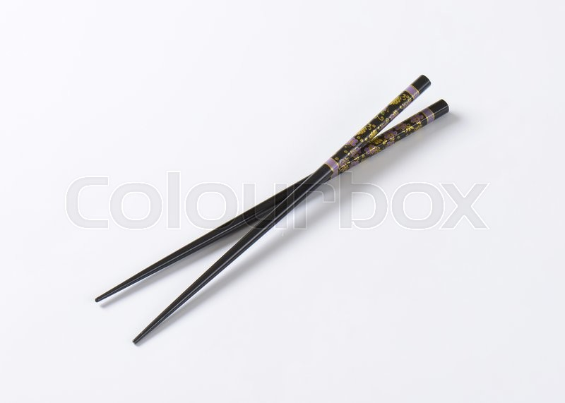 Stock image of 'A pair of black chopsticks with floral pattern'