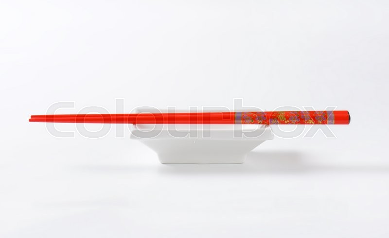 Stock image of 'A pair of red chopsticks on empty soy sauce dish'