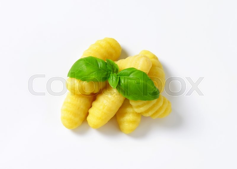 Stock image of 'Cooked potato gnocchi and fresh basil'