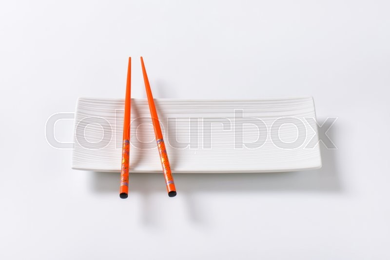 Stock image of 'A pair of orange chopsticks on empty white sushi plate'