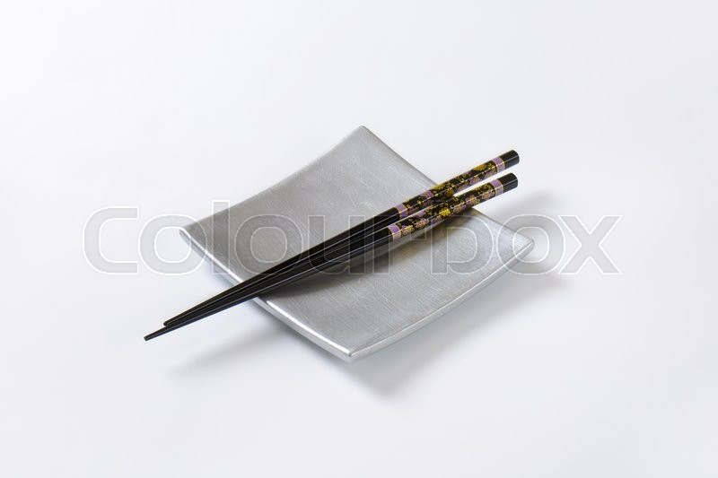 Stock image of 'A pair of black chopsticks on empty square silver sushi plate'