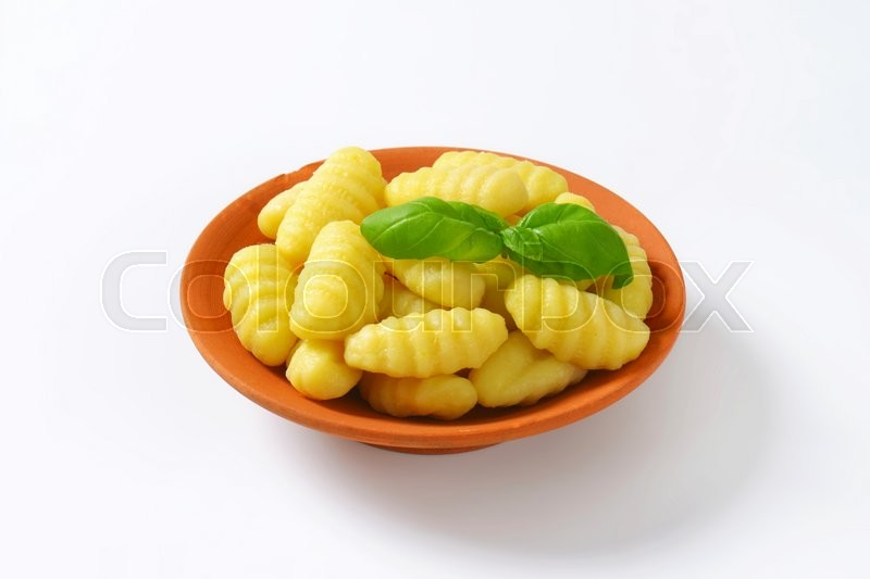 Stock image of 'Cooked potato gnocchi in terracotta dish'