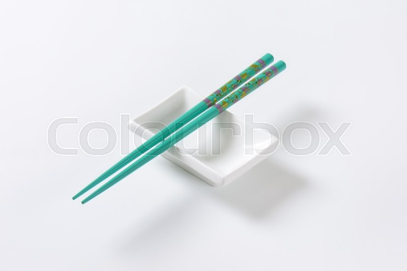 Stock image of 'A pair of blue chopsticks on empty soy sauce dish'
