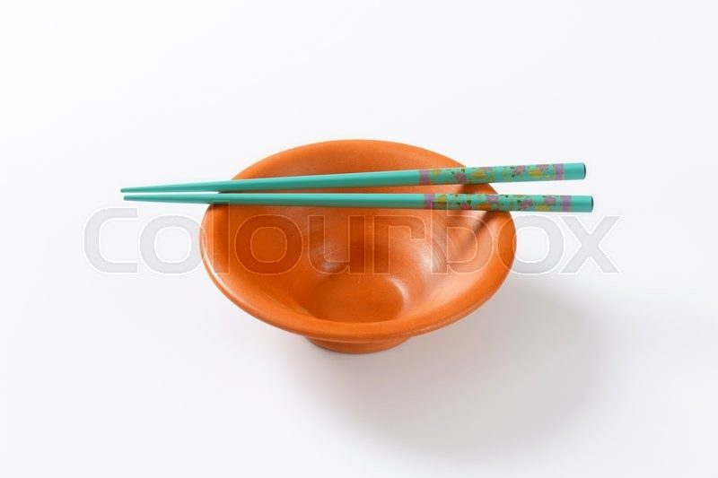 Stock image of 'A pair of blue chopsticks on empty terracotta bowl'