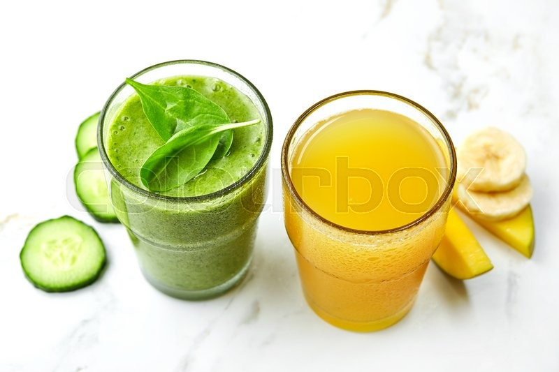Stock image of 'Glasses of green smoothie and yellow juice'