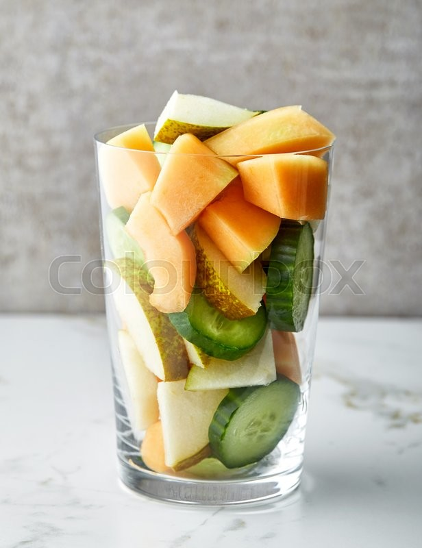 Stock image of 'glass of fruit and vegetable pieces for making smoothie'