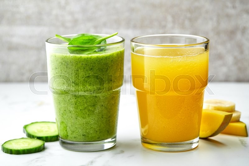 Stock image of 'green smoothie and yellow juice glasses on gray kitchen table'