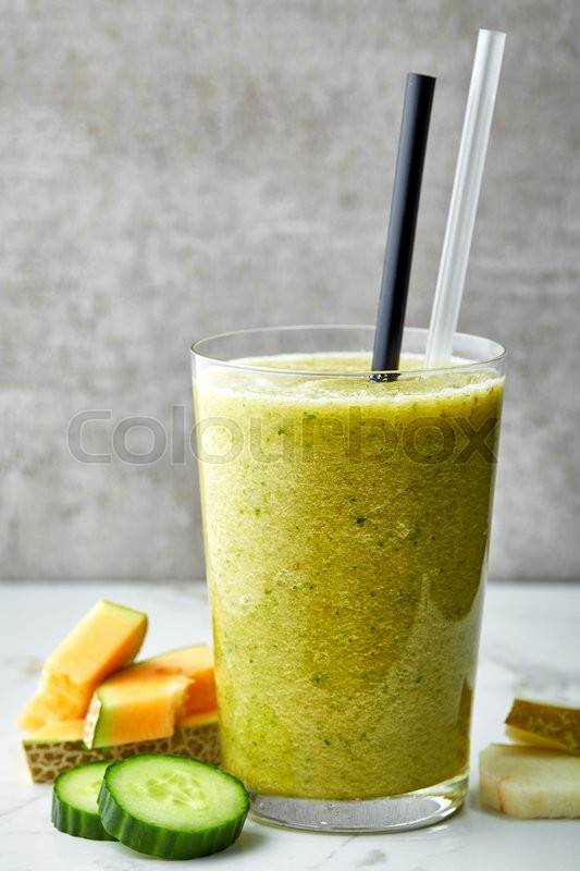 Stock image of 'glass of smoothie on gray kitchen table'
