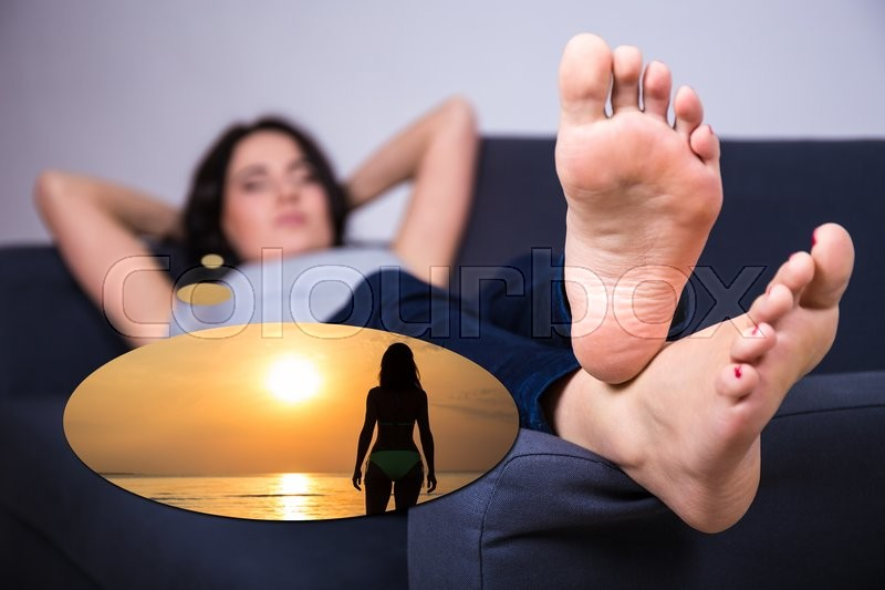Stock image of 'travel concept - young woman lying on sofa and dreaming about summer vacation'