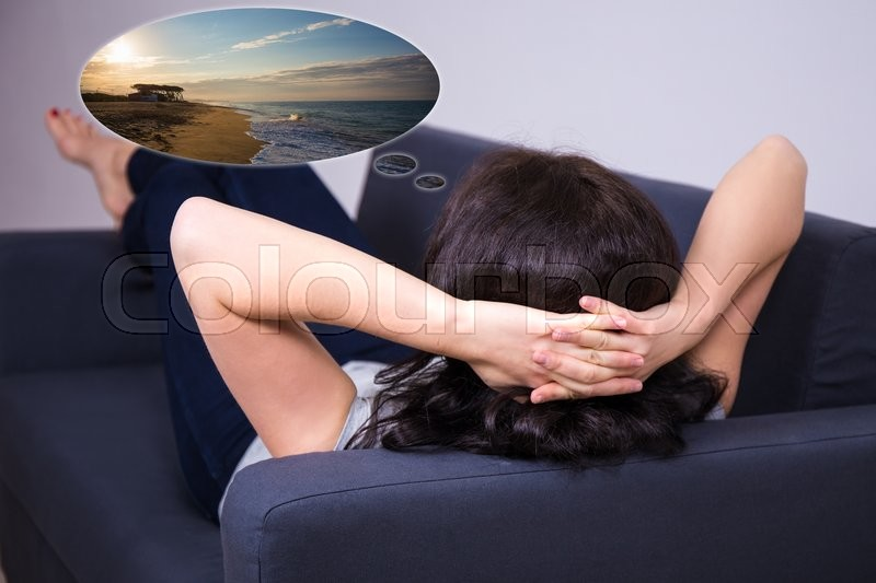 Stock image of 'back view of young woman lying on sofa and dreaming about summer vacation'