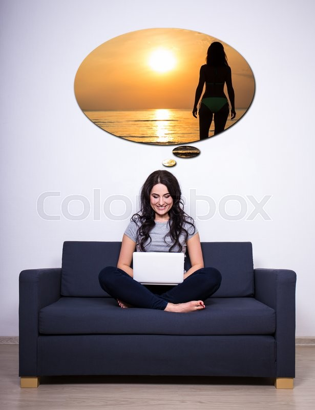 Stock image of 'woman sitting on sofa, using laptop and dreaming about summer at home'