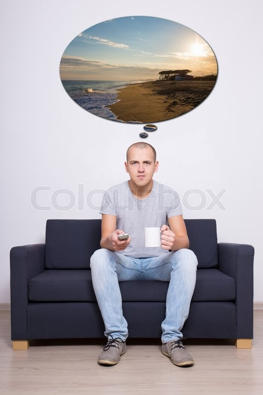 Stock image of 'travel concept - young handsome man sitting on sofa, watching tv and dreaming about vacation'