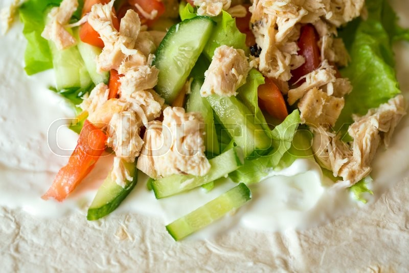 Stock image of 'Boiled chicken breast with fresh vegetables and sour cream in a pita'