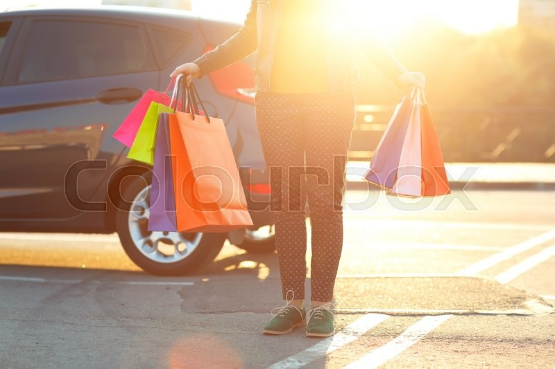 Stock image of 'Woman putting her shopping bags into the car - shopping concept'