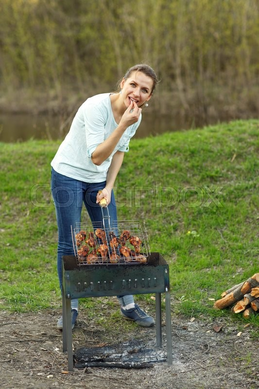 Stock image of 'Young pretty girl preparing food on grill'