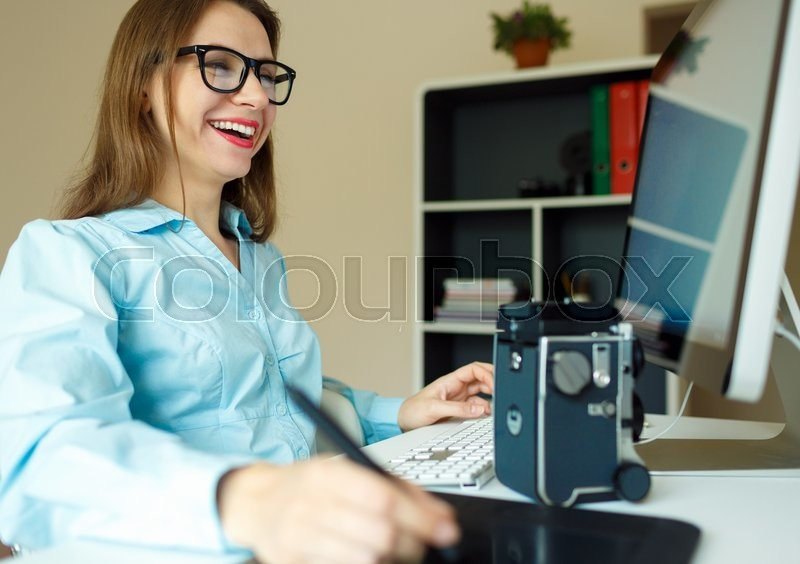 Stock image of 'Young woman artist drawing something on graphic tablet at the home office'