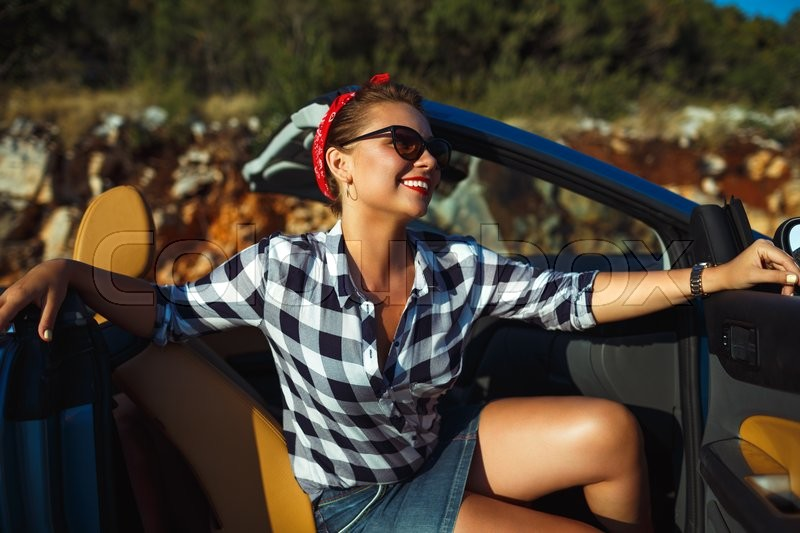 Stock image of 'Beautiful pin up woman sitting in cabriolet, enjoying trip on luxury modern car with open roof, fashionable lifestyle concept'