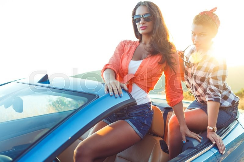 Stock image of 'Two young happy girls having fun in the cabriolet outdoors, summer vacation concept'