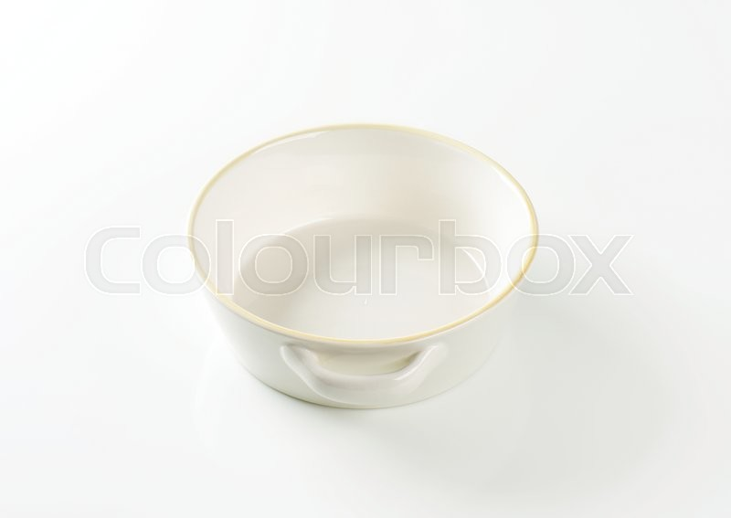 Stock image of 'Round white ceramic dish with side handles'