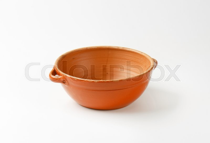 Stock image of 'Empty round red clay bowl with two small handles'