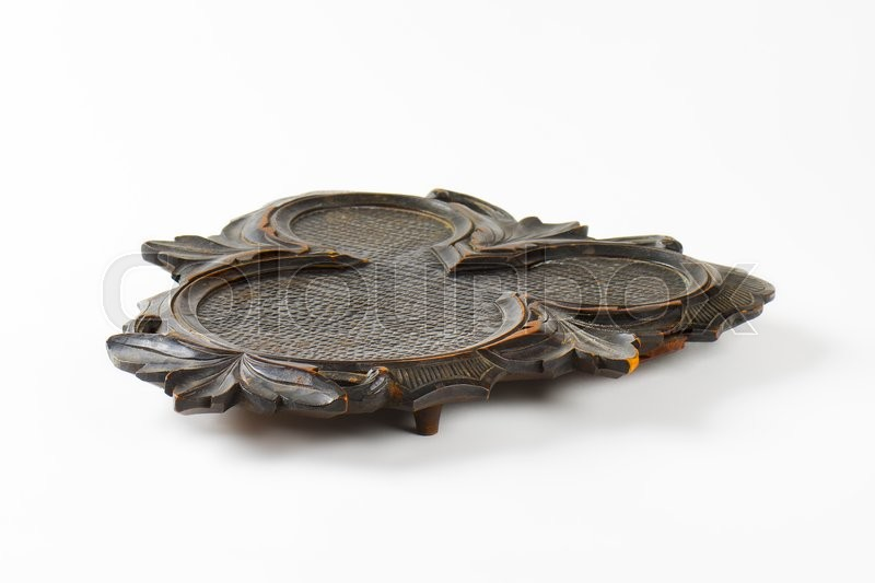 Stock image of 'Vintage hand carved wood trivet'