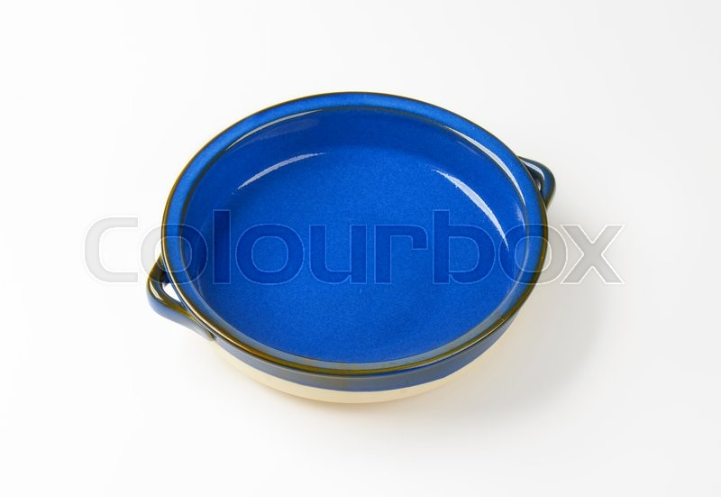 Stock image of 'Empty round ceramic baking dish with two handles'