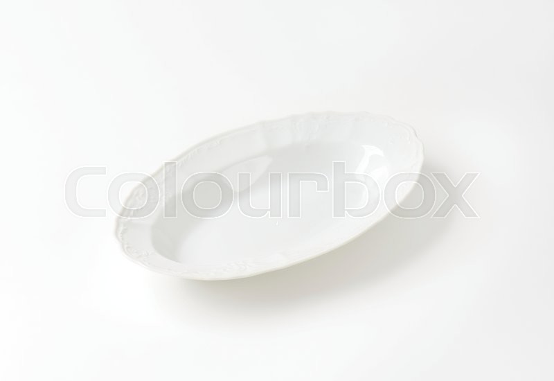 Stock image of 'Deep oval porcelain serving bowl with decorative rim'