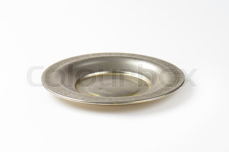 Stock image of 'Vintage metal saucer plate with decorative rim'