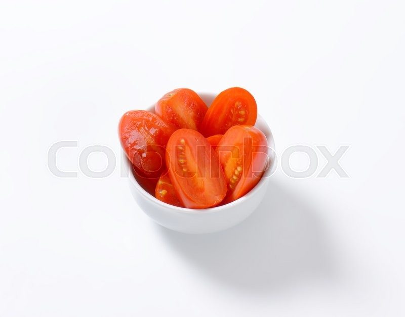 Stock image of 'Bowl of halved fresh Roma tomatoes'