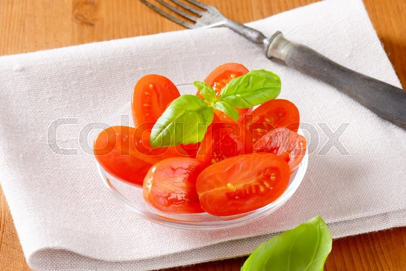 Stock image of 'Halved fresh oval-shaped red tomatoes on glass plate'