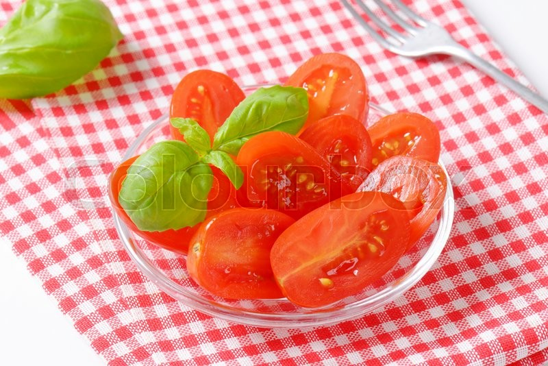 Stock image of 'Halved fresh Roma tomatoes on glass plate'